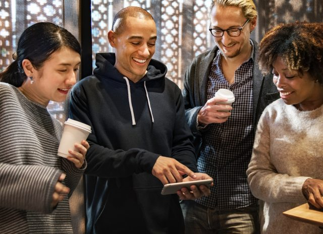 group of young people looking at smart phone and smiling